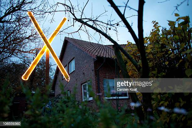 An illuminated X the traditional symbol of the 33 years old protest in this countryside against the nuclear waste transports stands in the garden of...