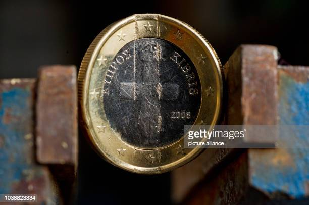 An illustrated picture shows a bent Cypriot euro coin clamped in a bench vice in Frankfurt Oder, Germany, 22 March 2013. Photo:PATRICK PLEUL   usage...