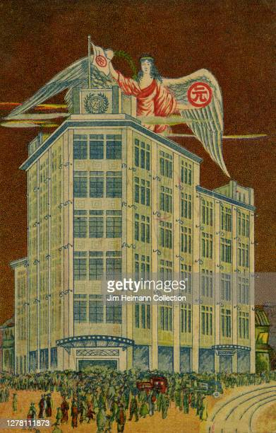 An illustration depicts a town in Japan where a crowd of people gather outside a tall building with a winged figure hovering above ca 1929