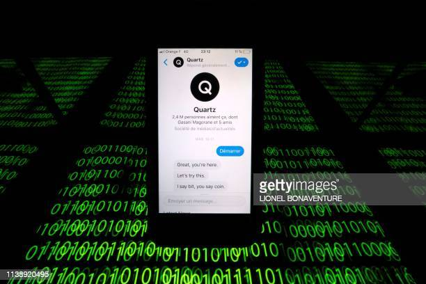 An illustration photo shows the Quartz chat bot displayed on a smartphone and a binary code displayed by a tablet in Paris on February 27 2019