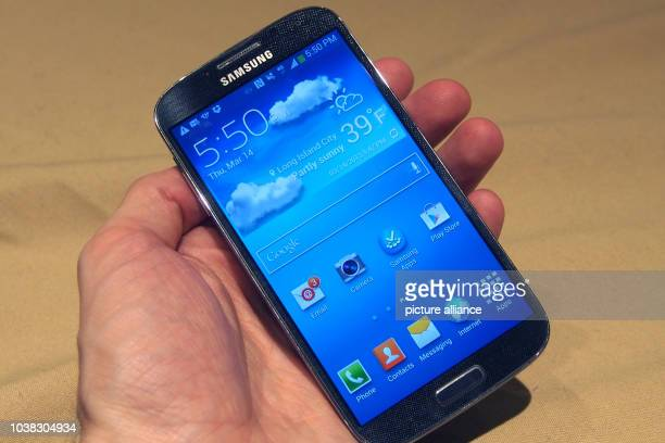 An illustration picture shows a journalist holding a new Samsung cell phone s4 in New York, US, 14 March 2013. New designed cell phone s4 is a...