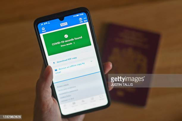 An illustration picture shows a smartphone screen displaying a Covid-19 vaccine record on the National Health Service app in London on May 18, 2021.