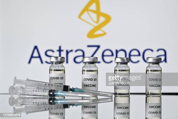 An illustration picture shows vials with Covid-19 Vaccine stickers attached and syringes with the logo of British pharmaceutical company AstraZeneca...