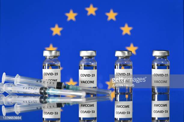 An illustration picture shows vials with Covid-19 Vaccine stickers attached, and syringes, with a flag of the European Union, on November 17, 2020.
