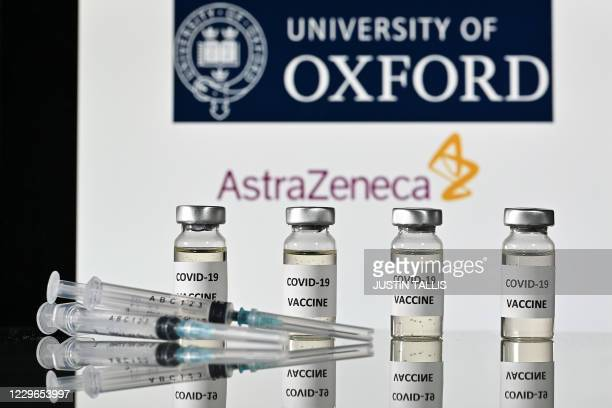 An illustration picture shows vials with Covid-19 Vaccine stickers attached and syringes, with the logo of the University of Oxford and its partner...