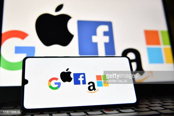 An illustration picture taken in London on December 18, 2020 shows the logos of Google, Apple, Facebook, Amazon and Microsoft displayed on a mobile...