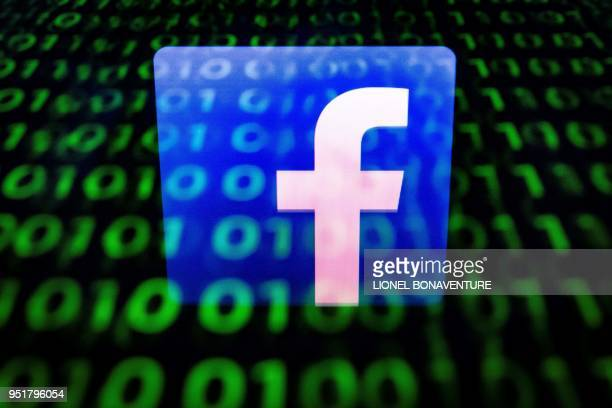 An illustration picture taken on April 26 2018 in Paris shows the logo of social network Facebook displayed on a screen and reflected on a tablet