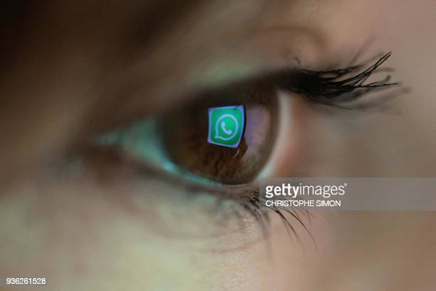 An illustration picture taken on March 22 2018 in Paris shows a closeup of the WhatsApp logo in the eye of an AFP staff member posing while she looks...