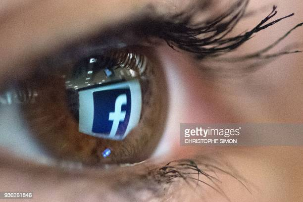 TOPSHOT An illustration picture taken on March 22 2018 in Paris shows a closeup of the Facebook logo in the eye of an AFP staff member posing while...