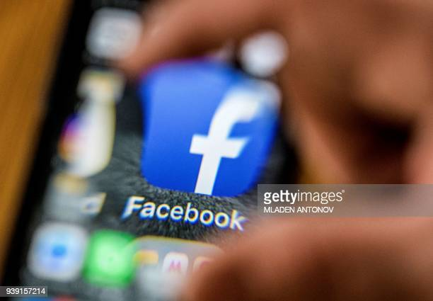 An illustration picture taken through a magnifying glass on March 28 2018 in Moscow shows the icon for the social networking app Facebook on a smart...