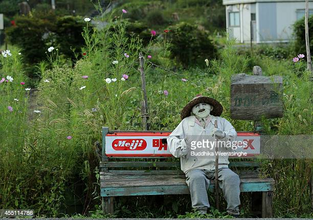 An illustration showing a scarecrow sitting on bench beside a road at Kakashi no Sato or the Scarecrow's Hometown on September 10 2014 in Himeji...