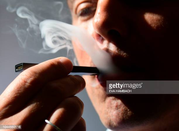 An illustration shows a man exhaling smoke from an electronic cigarette in Washington, DC on October 2, 2018. - In just three years, the electronic...