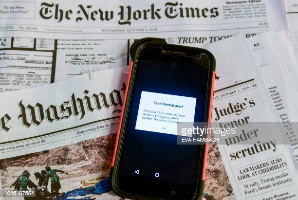 An illustration shows a smart phone atop newspapers displaying a Presidential alert in Washington DC October 3 2018 The Federal Emergency Management...