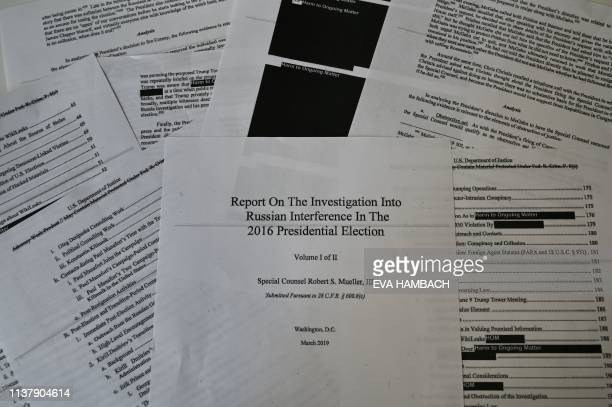 TOPSHOT An illustration shows printed pages of the redacted Mueller Report at an office on April 18 in Washington DC US Attorney General Bill Barr...