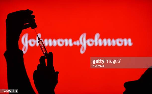 An illustrative image of a hand holding a medical syringe in front of the Johnson and Johnson logo displayed on a screen. On Monday, February 1 in...