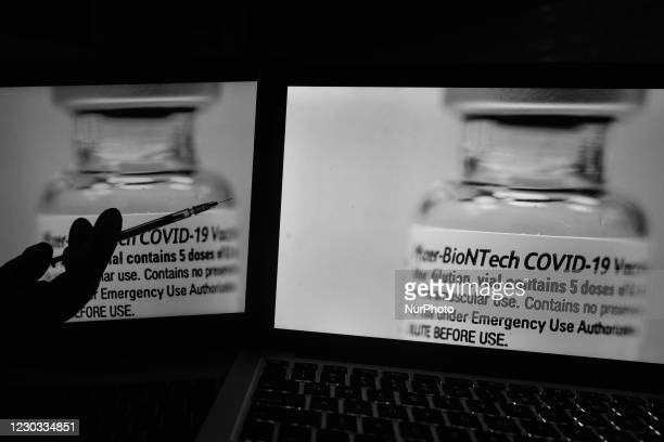 An illustrative image of a medical syringe in front of an image of a vial containing Pfizer-BionTech vaccine displayed on screens. On Monday,...