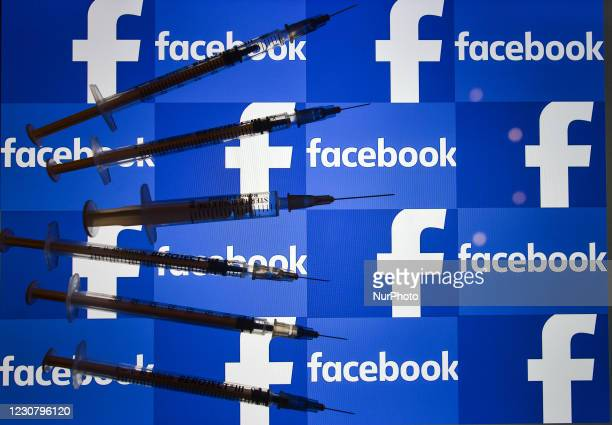 An illustrative image of medical syringes in front of a Facebook logo displayed on a screen. On Tuesday, January 26 in Dublin, Ireland.