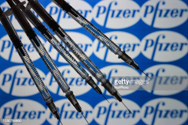 An illustrative image of medical syringes in front of a Pfizer logo displayed on a screen. On Tuesday, January 26 in Dublin, Ireland.