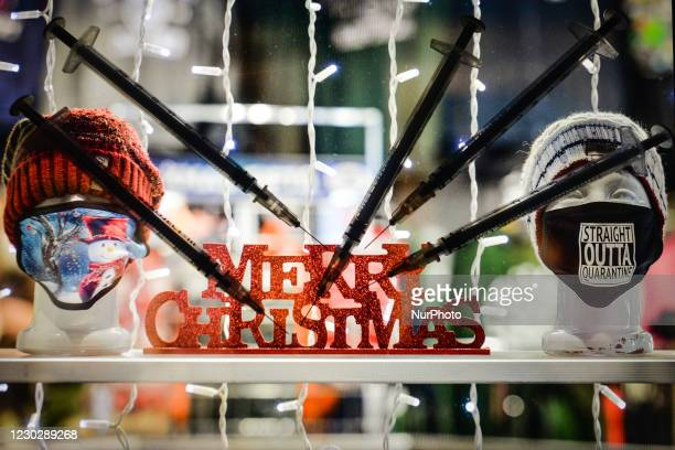 An illustrative photo showing medical syringes seen in front of a shop window decorated for Christmas displayed on a screen in the background on...