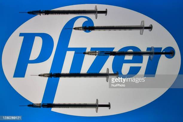 An illustrative photo showing medical syringes seen in front of Pfizer logo displayed on screens in the background on Christmas Eve. On Thursday,...