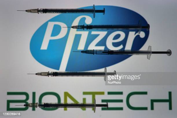 An illustrative photo showing medical syringes seen in front of Pfizer-BionTech logo displayed on screens in the background on Christmas Eve. On...