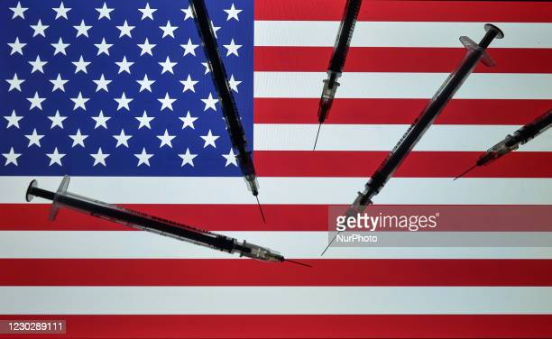 An illustrative photo showing medical syringes seen in front of the national flag of the United States of America, displayed on a screen in the...
