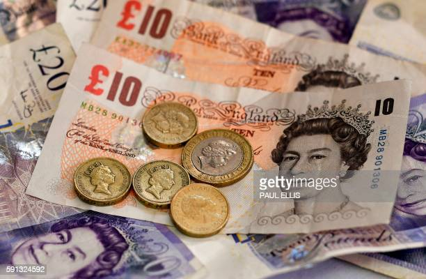 An illustrative picture taken in Liverpool on August 17 2016 shows an arrangement of British 10 and 20 pound bank notes and 1 and 2 pound coins From...