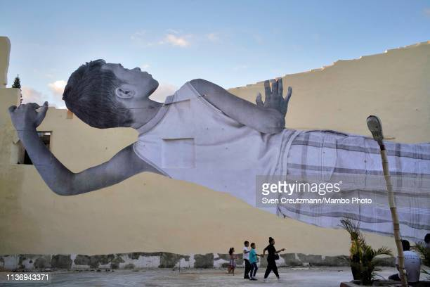 An image by French artist JR called Giants is displayed of a boy looking over a wall during the 13th Havana Biennial on April 13 2019 in Havana Cuba...