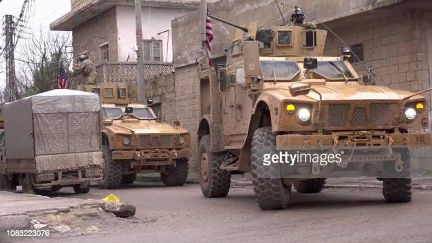 An image grab taken from a video obtained by AFPTV on January 16 shows US armoured vehicles at the scene of a suicide attack in the northern Syrian...
