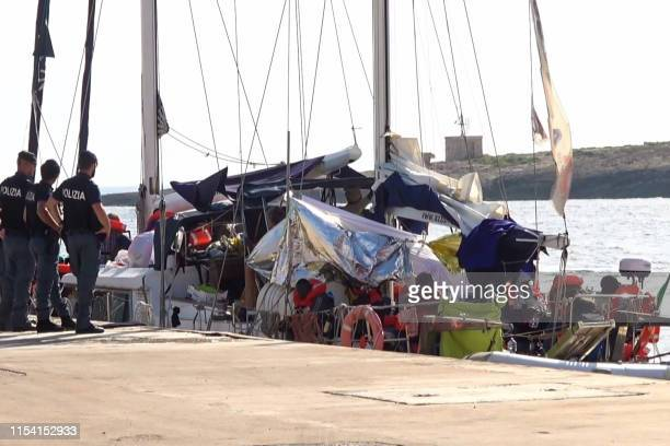 An image grab taken from a video released by Local Team on July 6 2019 shows Italian police officers standing guard by the charity sailboat that just...