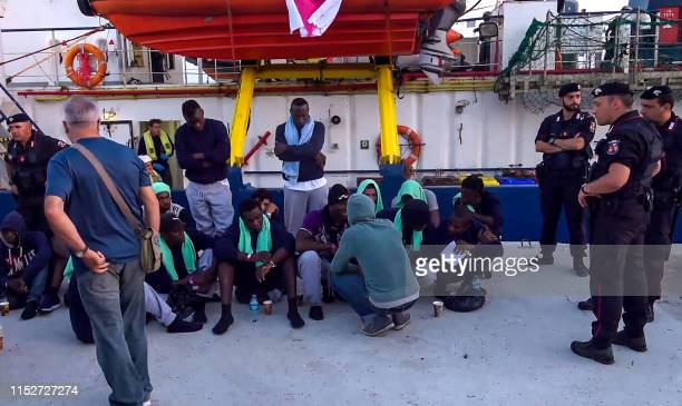 An image grab taken from a video released by Local Team on June 29 shows migrants disembarking from the SeaWatch 3 charity ship at the Italian port...