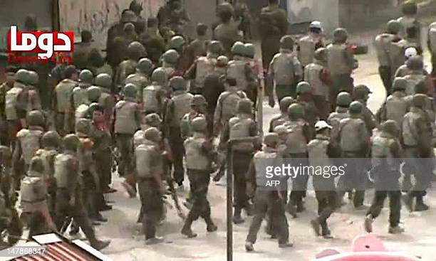 An image grab taken from a video uploaded on YouTube shows tens of Syrian troops deploying in the city of Duma in the Damascus region on April 30...