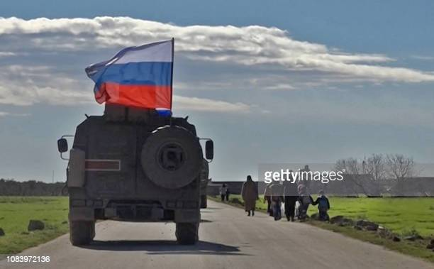 An image grab taken from AFP TV on January 17 shows a Russian army vehicle patrolling past people walking on the side of the road in the area of...