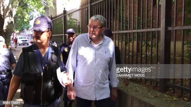 An image grab taken from AFPTV video footage shows convicted Dutch arms dealer Guus Kouwenhoven walking with police officers after appearing in court...