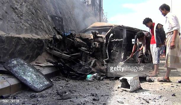 An image grab taken from an AFP video shows Yemenis inspecting the wrecked car of the governor of Yemen's second city Aden Jaafar Saad after a blast...