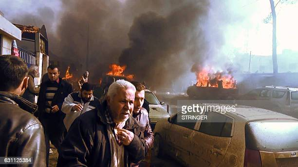 An image grab taken from an AFPTV video released on January 7 2017 shows people gathering amidst the debris at the site of a car bomb attack in the...