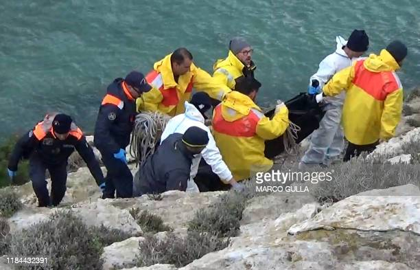 An image grabbed from a video shows a policeman forensic police officers and rescuers carrying a migrant's dead body in a plastic dead body bag on...