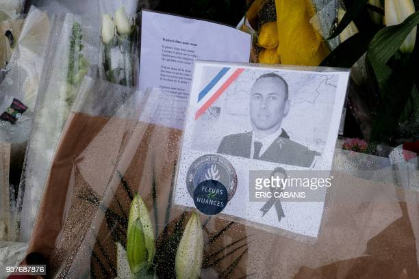 An image LieutenantColonel Arnaud Beltrame is attached to a bouquet of flower laid outside the gates of the gendarmerie of Carcassonne where he...