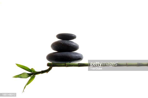an image of 3 stacked stones balancing on bamboo - feng shui stock photos and pictures