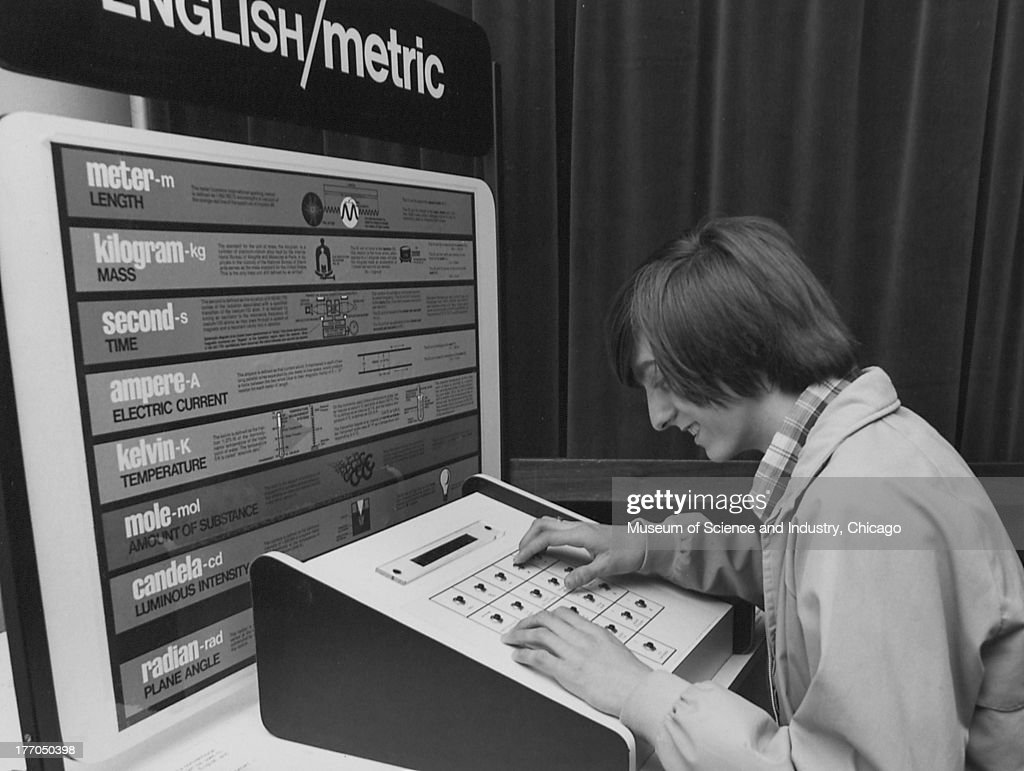 A Boy Interacts With A English/Metric Exhibit : News Photo