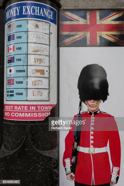 An image of a guardsman and a money exchange list that once displayed foreign currencies and their values on 3rd February 2017 in London England