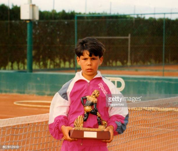 An image of a photograph depicting a young Rafael Nadal holding a trophy he won in his childhood displayed at the 'Club Tenis Manacor' in Majorca...