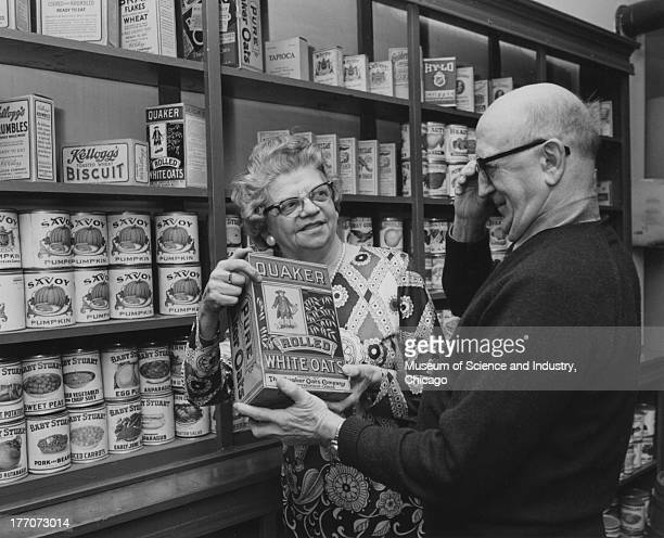 An image of a replica of an early general store depicting two seniors looking at an early style box of Quaker Oats during the Senior Citizens Night...
