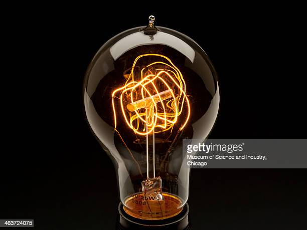 An image of a reproduction early 20th century Victorian style clear light bulb with glowing exposed quad looped tungsten filament from a collection...