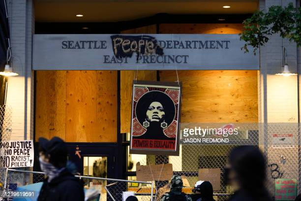 An image of activist Angela Davis is displayed above the entrance to the Seattle Police Department's East Precinct vacated June 8 and now surrounded...