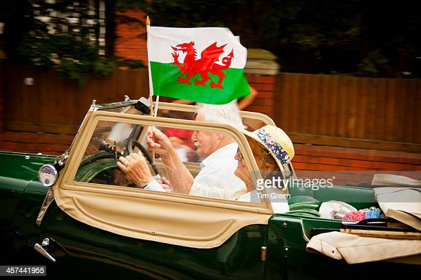 An image of an elderly patriotic couple driving past in their vintage car, with the lady passenger waving the Welsh flag with an obvious sense of...