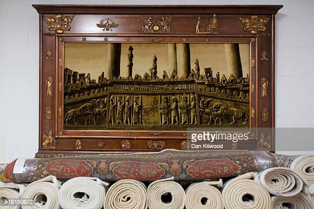 An image of ancient Persepolis hangs above Persian Rugs at the Oriental Rug Centre's main warehouse on March 17 2016 in London England The Oriental...