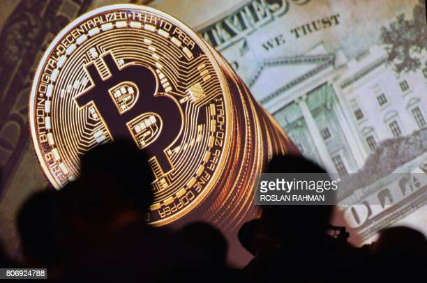 An image of Bitcoin and US currencies is displayed on a screen as delegates listen to a panel of speakers during the Interpol World Congress in...