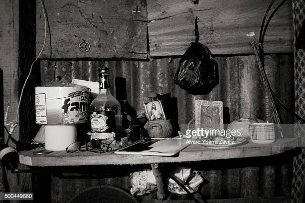 An image of Christ sits alongside a bottle of liquor which acts as a metaphor for the lives and broken dreams of the guaqueros Don Arturo is a...