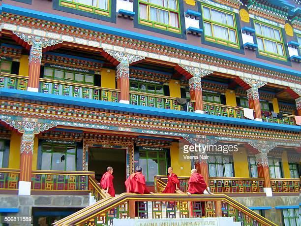 CONTENT] An image of colourful Karma Shri Nalanda Institute at Rumtek Monastery Sikkim Buddhist Monks share a light moment outside the institute